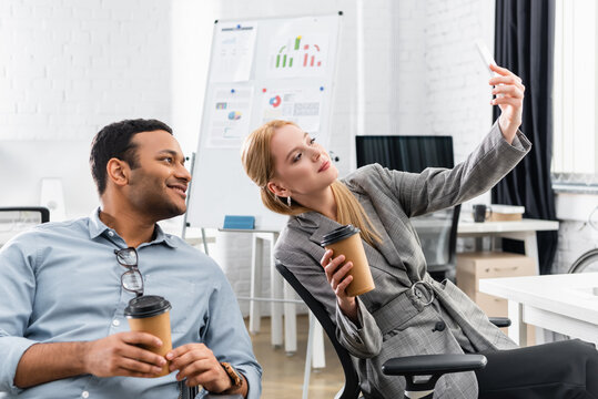 Businesswoman taking selfie with indian colleague holding takeaway drink in office
