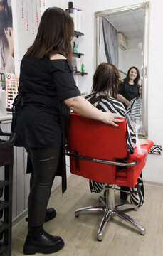 Hairdresser making hairstyle. Cheerful hairdresser working with her client at the small beauty salon.