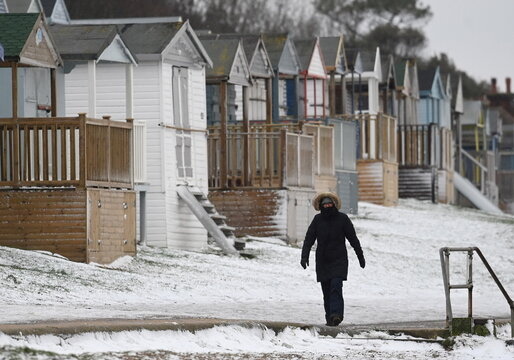 A woman walks along the seafront at Whitstable, as Storm Darcy affects large parts of the country, Whitstable, Britain