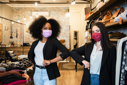 Portrait of two beautiful owners of clothing store who greet each other and give strength by touching elbows - Millennial salespeople wear protective masks against Coronavirus infection, Covid-19