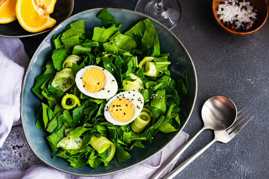 Bowl of spinach salad with cucumber, eggs and sesame seeds and orange wedges