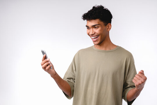 Young attractive african man is happy as a winner with smart phone isolated over white background