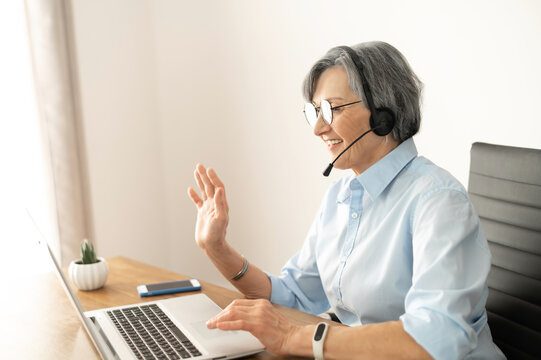 Mature female entrepreneur in glasses and a headset is sitting at the desk in home office and waving at the laptop screen, participating in an online virtual conference, chatting with teammates