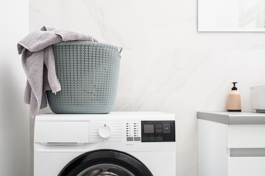 Laundry basket on automatic washing machine in bathroom