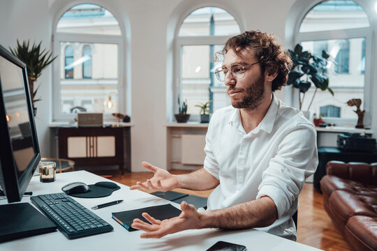 Portrait of a confused office worker which looks at computer screen and throws his hands not knowing what to do in office room.