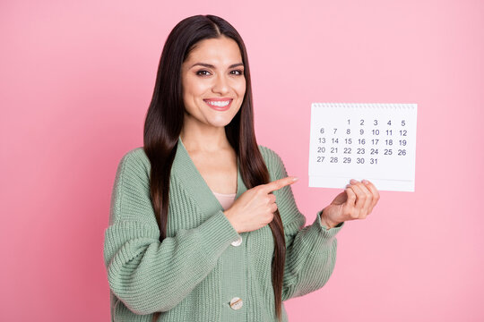 Photo of lady hold calendar direct finger date wear green cardigan isolated pastel pink color background