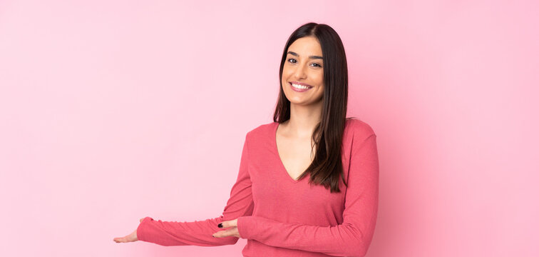 Young caucasian woman over isolated background extending hands to the side for inviting to come