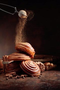 Freshly baked sweet buns sprinkled with cinnamon powder.