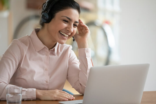 Happy consultant in headphones using laptop for video call and laughing. Female tutor teaching class online from home, holding webinar, smiling at webcam. Young Indian operator giving client support