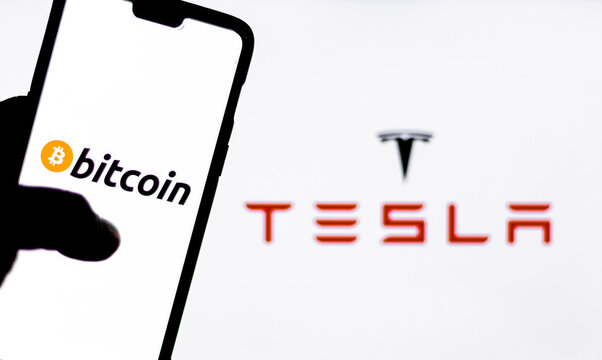 Bitcoin logo on a smartphone against Tesla logo in the background. Elon Musk recently invested $1.5 billion in Bitcoin, opening possibility of Bitcoin transactions to purchase Tesla automobiles.