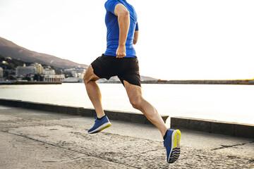 Wall Mural - back male runner run in morning along sea embankment in city