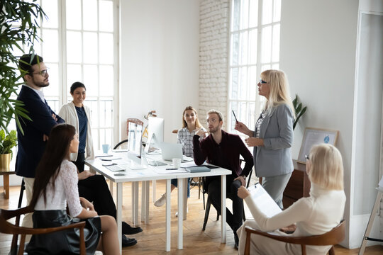 Corporate coach giving workshop or consultation to employees. Senior manager holding meeting or brainstorming. Middle aged female business leader discussing project with team in boardroom.