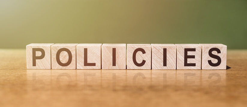 POLICIES word written on wooden blocks on wooden table. Concept for your design.