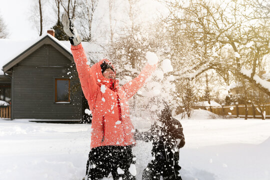 Young woman throwing snow in the air while playing with her kid son near home in deep snow.