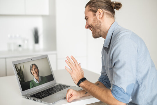 A guy waving hand, greeting with a senior woman on the laptop screen, student talking on virtual meeting with elderly female tutor, an adult son calls to mother via video call. Social distancing