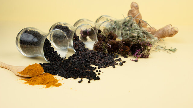 Immunity booster concept. Dried berries and herbs for enhanced health. Turmeric, elderberry, barberry, astragalus, echinacea, ginger on light yellow background.