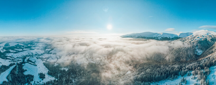 180 degree panoramic view of foggy snow-capped mountains during sunrise. Fantastic morning winter landscape.