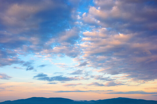 cloudscape in summer at sunrise. clouds on the blue sky in yellow and pink morning light. idyllic weather condition, picturesque scenery above the mountain ridge