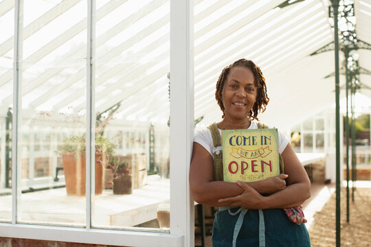 Portrait female garden shop owner with open sign in greenhouse