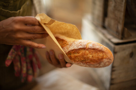 Close up female baker holding fresh baked baguette bread