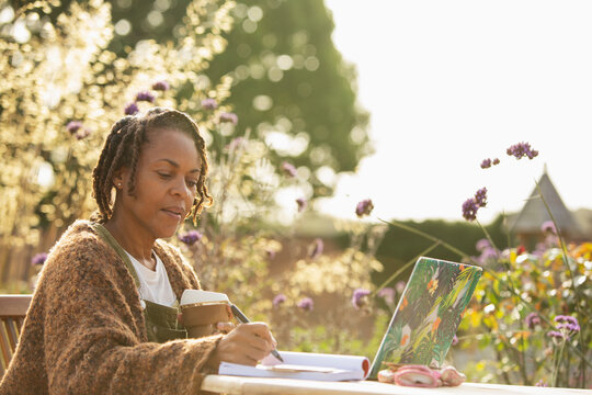 Woman with coffee working at laptop on sunny garden patio