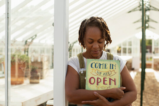 Portrait female garden center owner with open sign in greenhouse