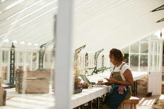 Female garden shop owner working at laptop in greenhouse