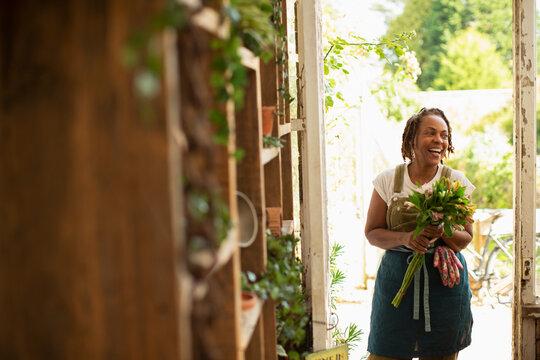 Happy female florist with flower bouquet in shop doorway