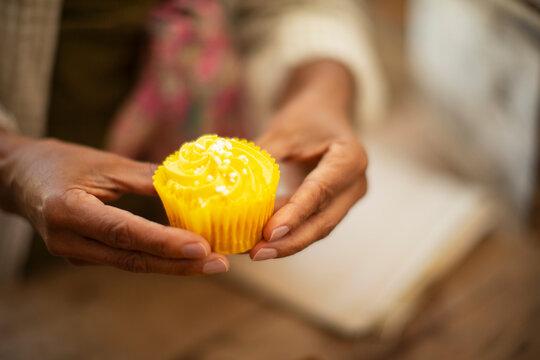 Close up woman holding bright yellow lemon cupcake