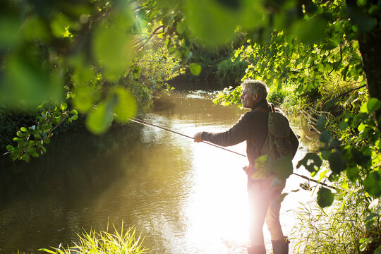 Man fly fishing at sunny idyllic summer riverbank