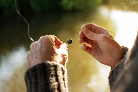 Close up man preparing weight on fly fishing line