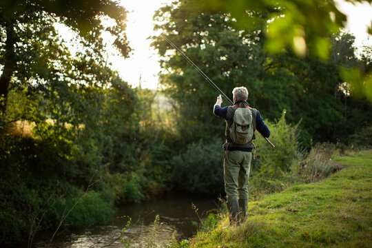 Man in backpack fly fishing at riverbank