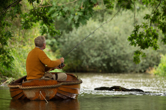 Man fly fishing from boat on river