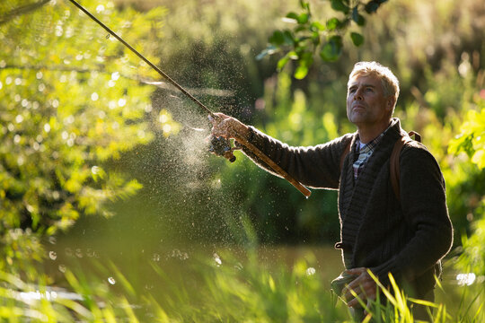 Man casting fly fishing pole at sunny green river