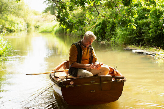 Man fly fishing and using smart phone in boat on river
