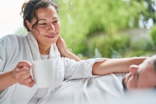 Happy couple drinking coffee talking in bed