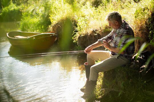 Man fly fishing rolling up sleeves at sunny riverbank