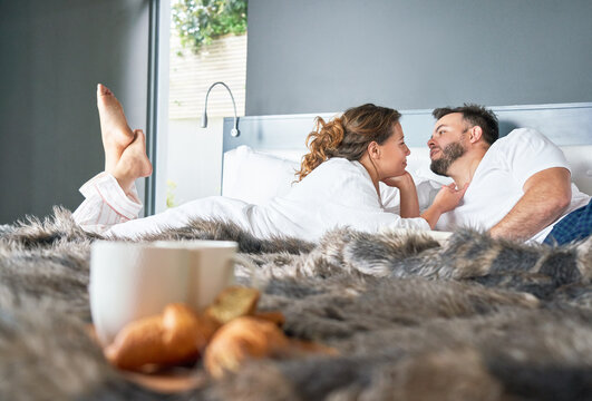 Affectionate couple talking on morning bed