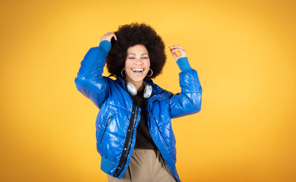 Young African American woman - ballerina dancing. Designer woman with curly hair in blue suit showing some movements. The concept of sport, dance and urban culture.