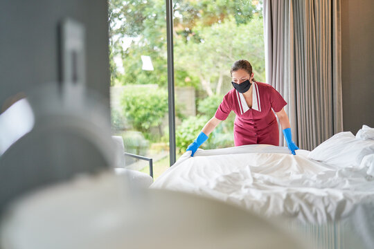 Female hotel maid in face mask making bed in hotel room