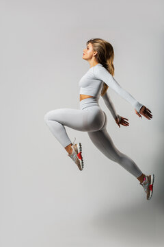 attractive woman in sportswear jumping on white background