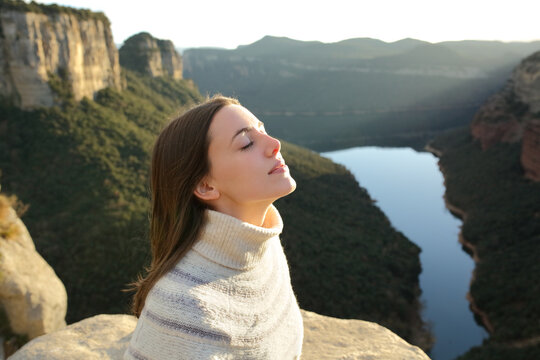 Woman breathing fresh air in a cliff in the mountain