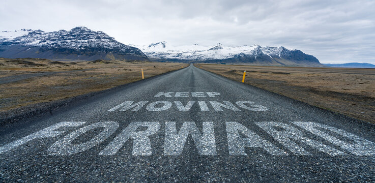 Keep moving forward text quote written on asphalt road leading towards infinity and mountain scenery in the background.