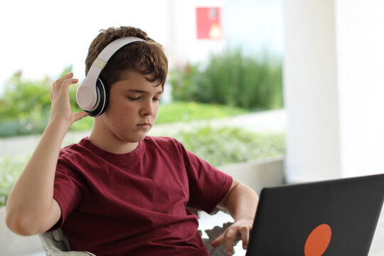 preteen boy using notebook and headset