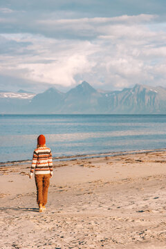 Woman walking on sandy beach travel alone in Norway summer trip active lifestyle vacations outdoor