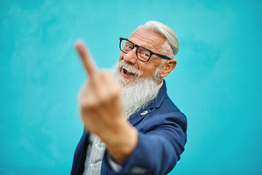 Older hipster man in positive attitude with angry facial expression shows fuck you. - Focus on the face
