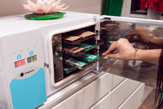 The master puts the manicure tools into the sterilizer. Sterilization of instruments in a beauty salon. Sterilization. Equipment for sterile cleaning of working manicure tools.