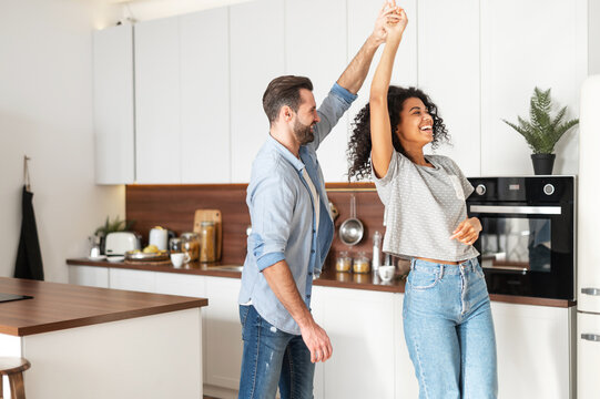Handsome white man and attractive African American young woman is cooking and having fun together while cooking on the kitchen, romantic interracial couple is dancing while preparing lunch or dinner