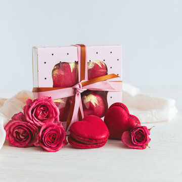 Heart-shaped macaroons with pink rose and gift box on a white wooden background. Concept for Valentine's Day.