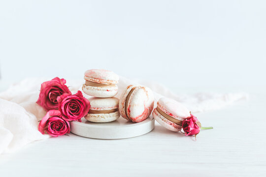 Tasty french macaroons with pink roses on a plate. White background.